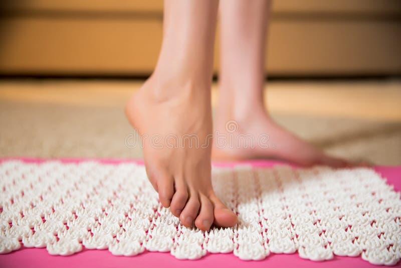站立在针压法席子的女性脚 免版税图库摄影