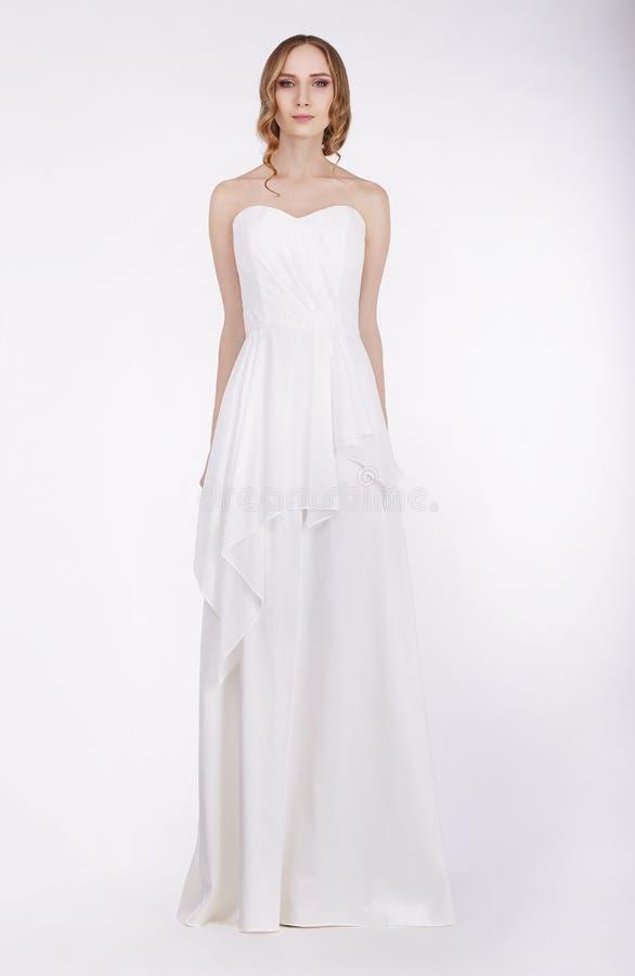 站立在长的白色礼服的时装模特儿 库存照片