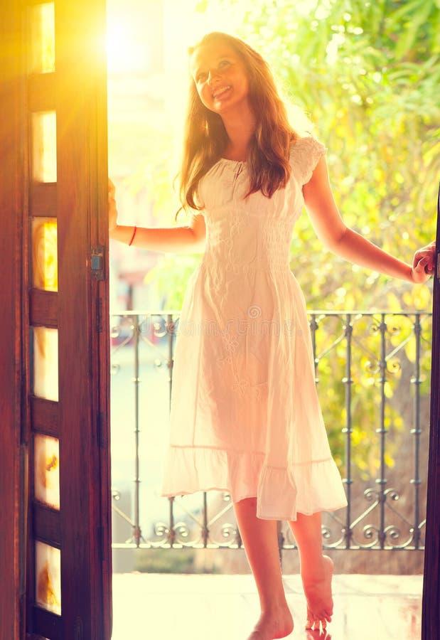 站立在门户开放主义的白色礼服的秀丽十几岁的女孩 免版税图库摄影