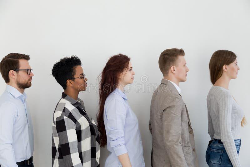 站立在队列等待工作面试的候选人近的墙壁 免版税库存图片