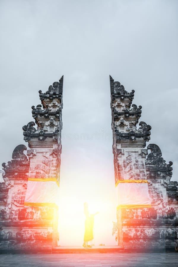 站立在阳光的妇女剪影 Lempuyang寺庙,巴厘岛印度尼西亚 库存照片