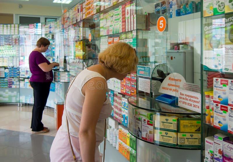 站立在阿卢什塔药房的窗口的真正的人民的买家  库存图片