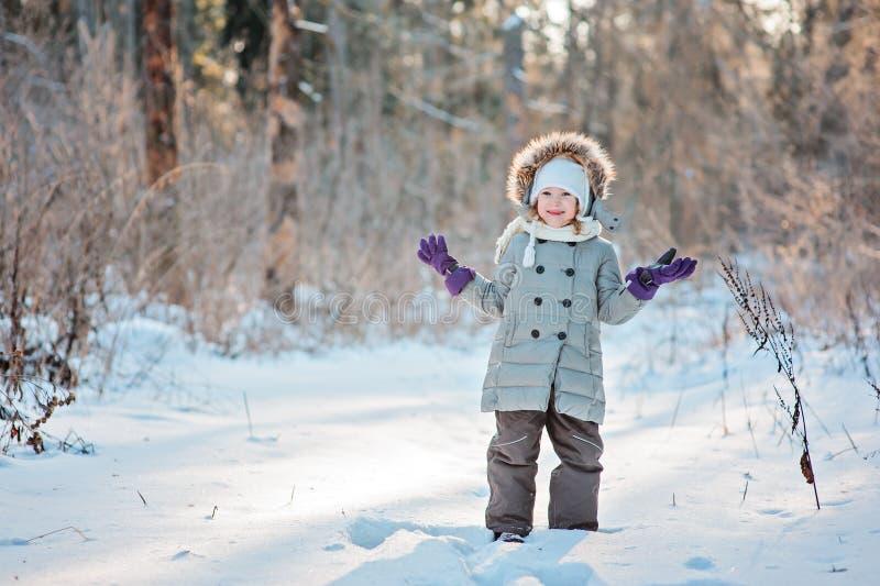 站立在雪的逗人喜爱的微笑的儿童女孩在冬天晴朗的森林里 免版税图库摄影
