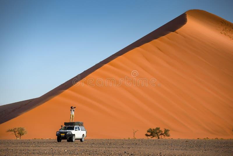 站立在露营车汽车的年轻亚裔人旅客在橙色沙子附近 免版税图库摄影