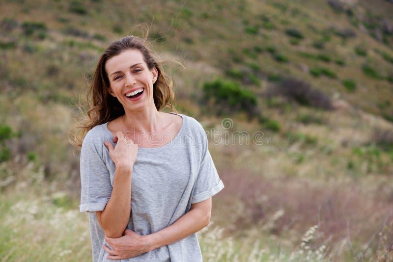 站立在领域的健康笑的妇女外面 库存照片