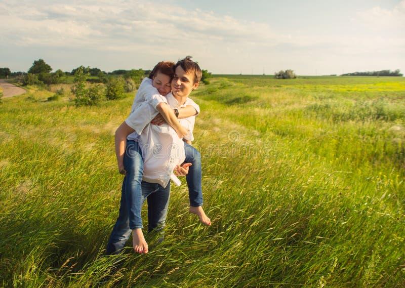 站立在领域的愉快的夫妇在日落 免版税库存照片