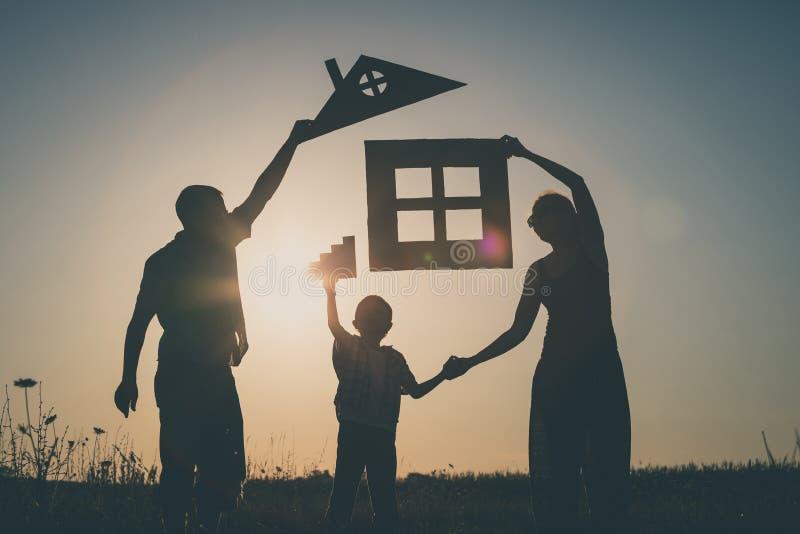 站立在领域的愉快的家庭在日落时间 图库摄影