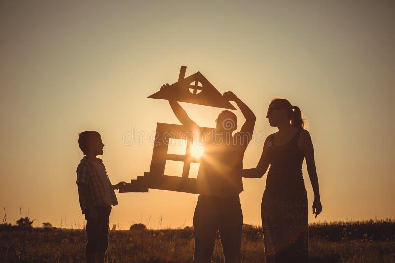 站立在领域的愉快的家庭在日落时间 免版税图库摄影