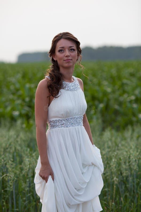站立在领域的白色婚礼礼服的微笑的妇女 库存照片
