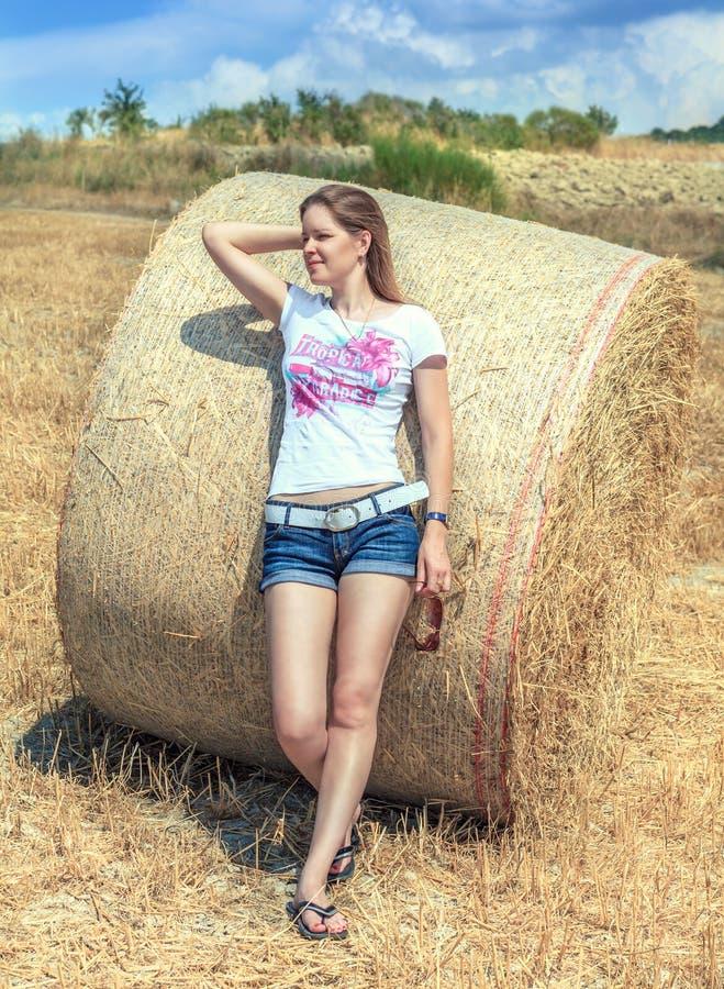 站立在领域的短的短裤的年轻美丽的女孩根据一个圆的大包干草和神色入距离 免版税库存图片