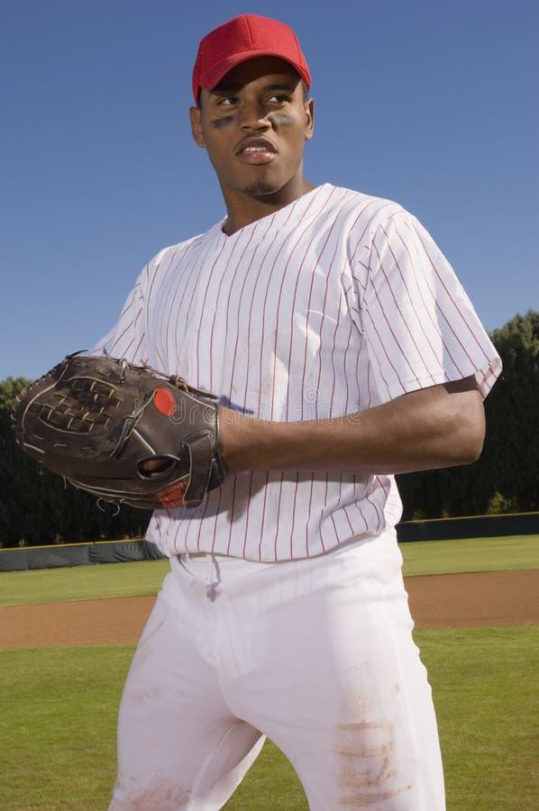站立在领域的年轻棒球投手 免版税库存照片