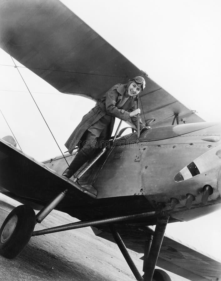 站立在飞机的翼的少妇(所有人被描述不更长生存,并且庄园不存在 供应商warra 免版税库存图片
