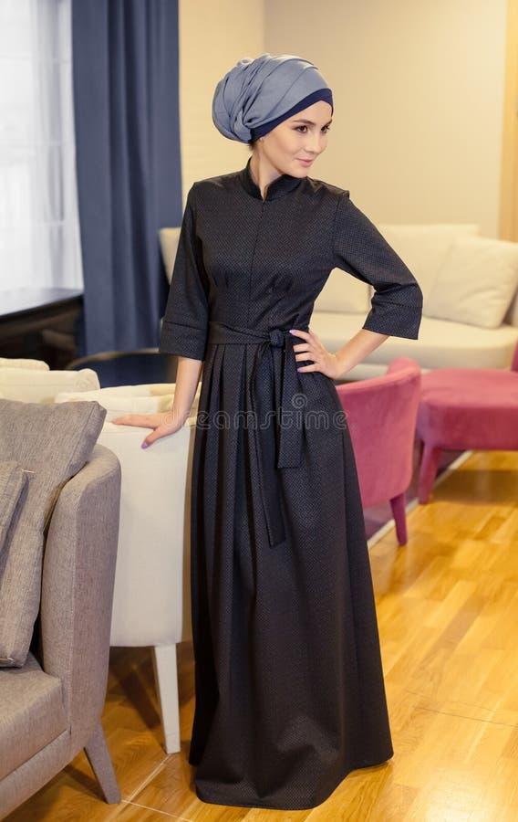 站立在餐馆的休息室的一件现代东方礼服的美丽的回教妇女 免版税库存照片