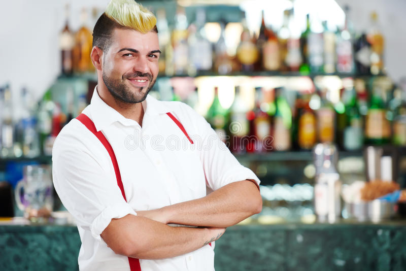 站立在餐馆酒吧的男服务员画象近的侍酒者书桌 免版税库存照片