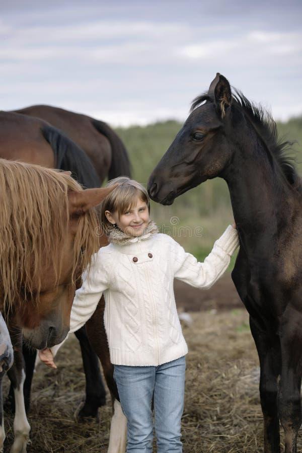站立在马中的一件白色毛线衣和牛仔裤的滑稽的愉快的孩子在农厂微笑产驹 生活方式画象 库存照片