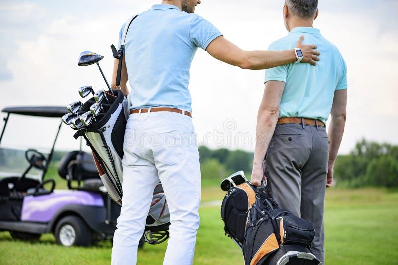 站立在高尔夫球场的比赛的两个伙伴 库存图片