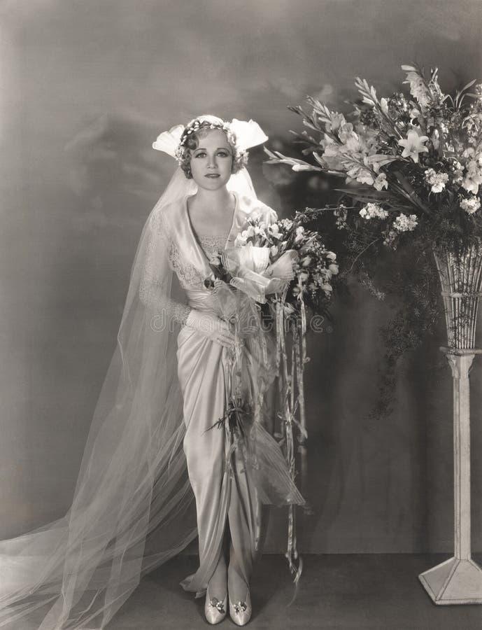 站立在高花瓶的新娘花旁边 图库摄影