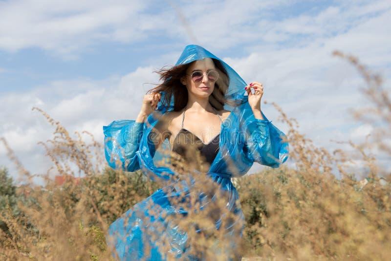 站立在高草和天空背景的年轻性感的女孩画象  她佩带的黑游泳衣、雨衣和太阳镜 免版税库存图片