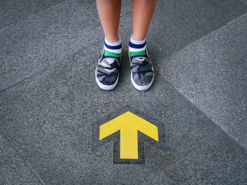 站立在黄色定向箭头前面的孩子的低部分 免版税库存照片