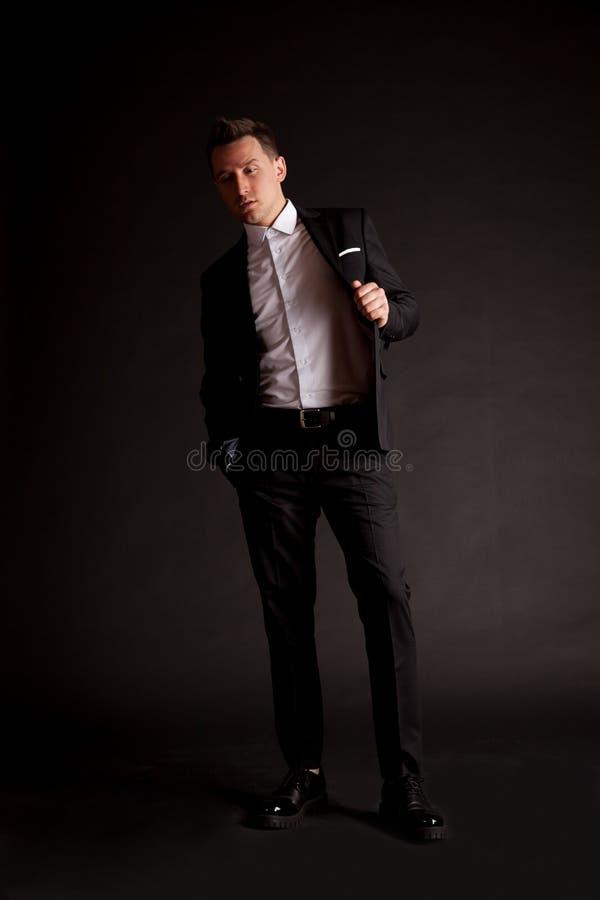 站立在黑背景前面的一个确信的典雅的英俊的年轻人在穿着好的衣服的演播室 免版税图库摄影