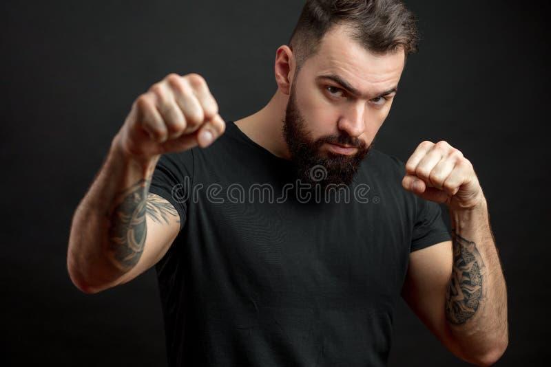 站立在黑背景的战斗的姿态的黑T恤杉的人 图库摄影