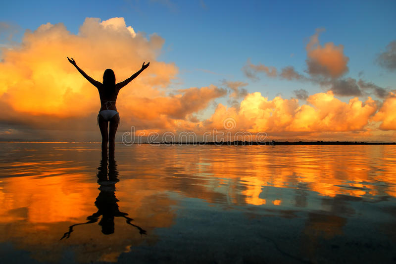 站立在水中的现出轮廓的妇女在塔韦乌尼岛Islan的日落 库存照片