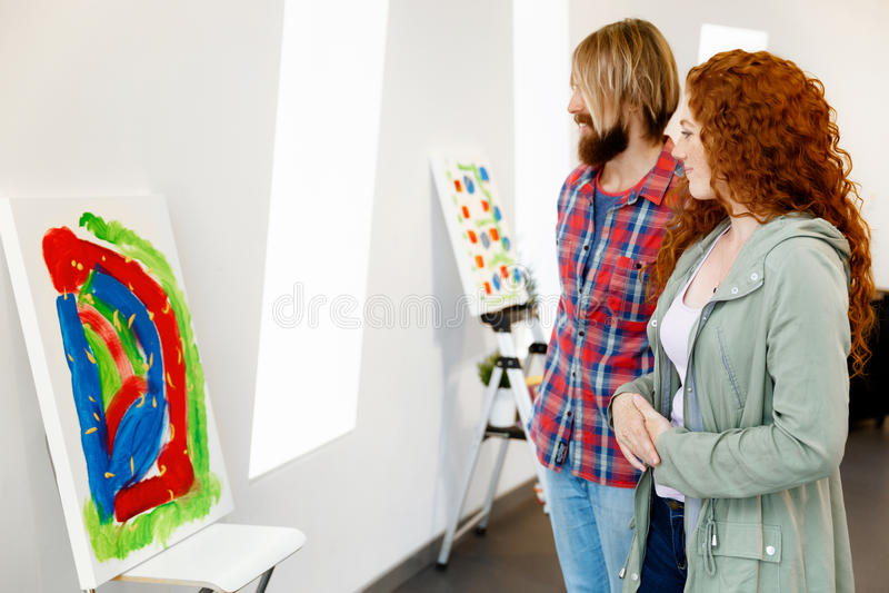 站立在画廊和冥想艺术品的年轻白种人夫妇 库存照片