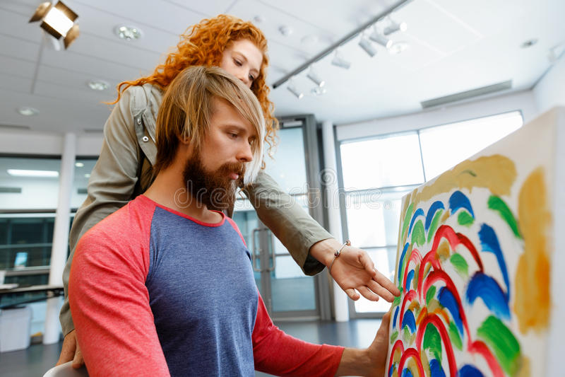 站立在画廊和冥想艺术品的年轻白种人夫妇 免版税库存图片