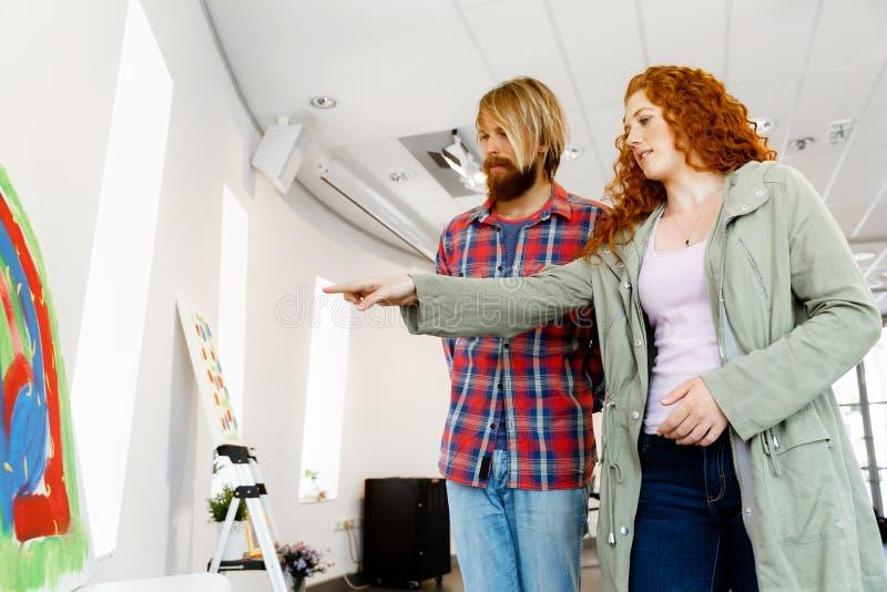 站立在画廊和冥想艺术品的年轻白种人夫妇 图库摄影