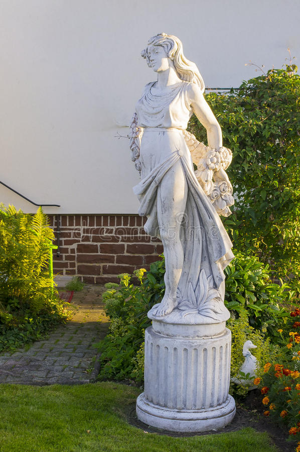 站立在围场的一个美丽的女孩的雕塑 免版税库存照片