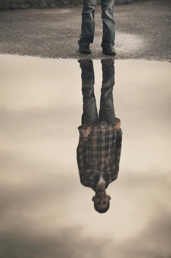 站立在水坑的小男孩 库存照片