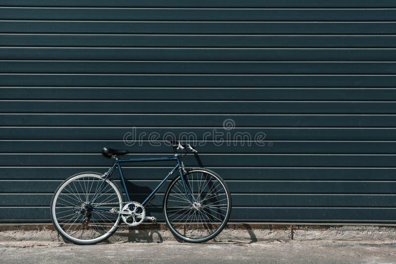 站立在黑墙壁附近的经典行家自行车户外 免版税库存照片