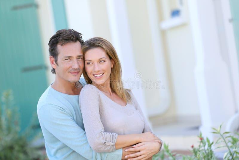 站立在他们新的家前面的愉快的中年夫妇 免版税库存照片