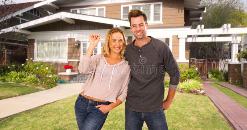 站立在他们新的家前面的激动的第一次购屋者 免版税库存图片