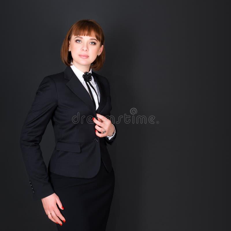 站立在黑暗的办公室室和看照相机的快乐的确信的女商人 黑色的迷人的女实业家 免版税库存照片