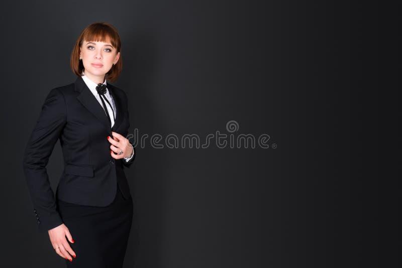 站立在黑暗的办公室室和看照相机的快乐的确信的女商人 黑色的迷人的女实业家 免版税库存图片