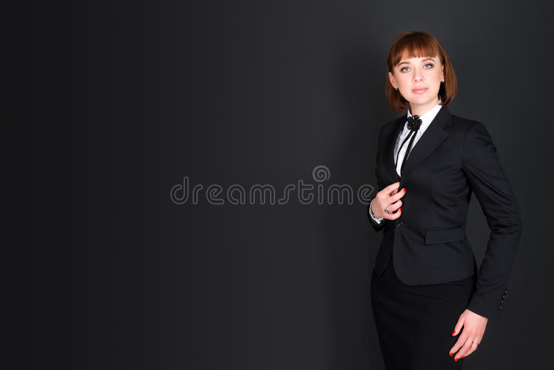 站立在黑暗的办公室室和看照相机的快乐的确信的女商人 黑色的迷人的女实业家 库存图片