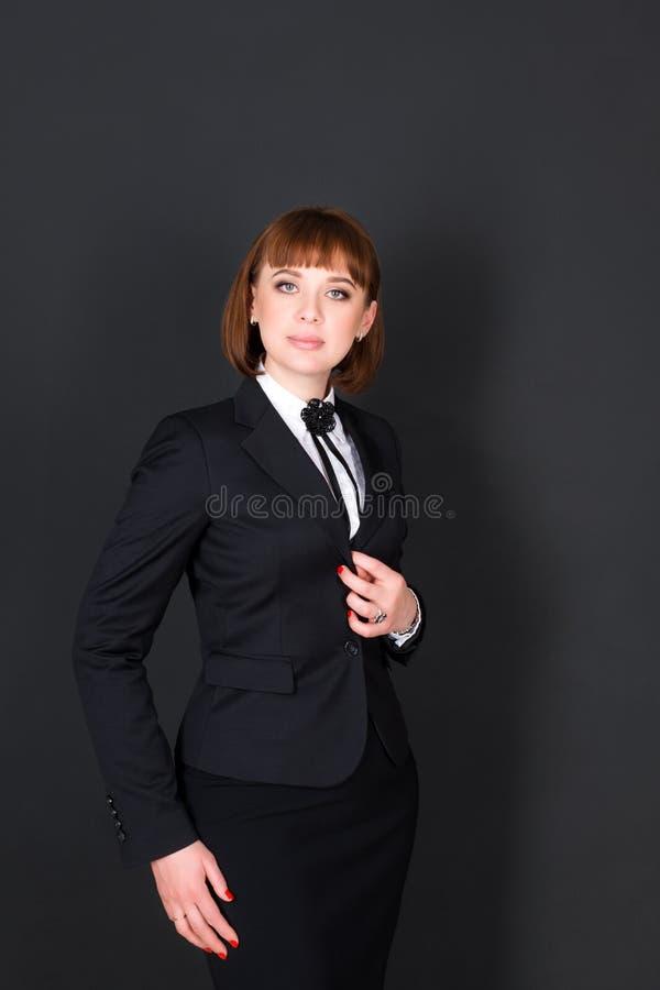 站立在黑暗的办公室室和看照相机的快乐的确信的女商人 黑色的迷人的女实业家 免版税图库摄影