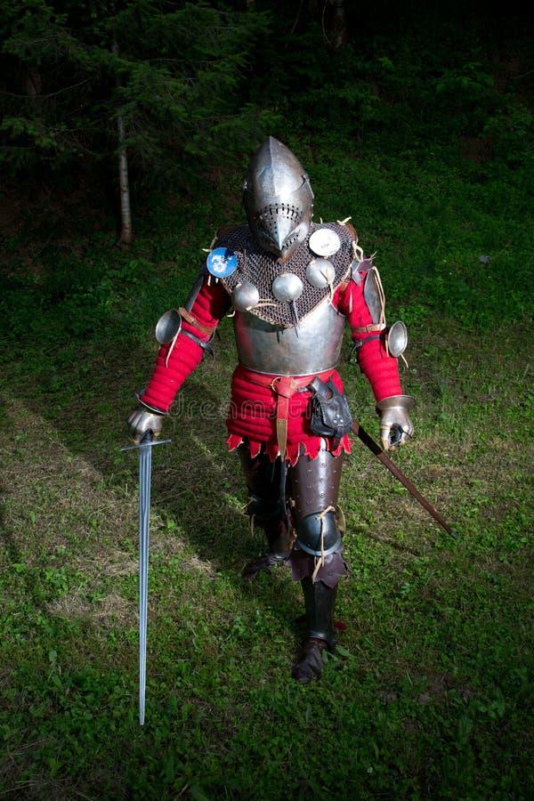 站立在黑暗的森林准备好争斗,全长射击里的骑士的衣服的中世纪战士 免版税库存图片