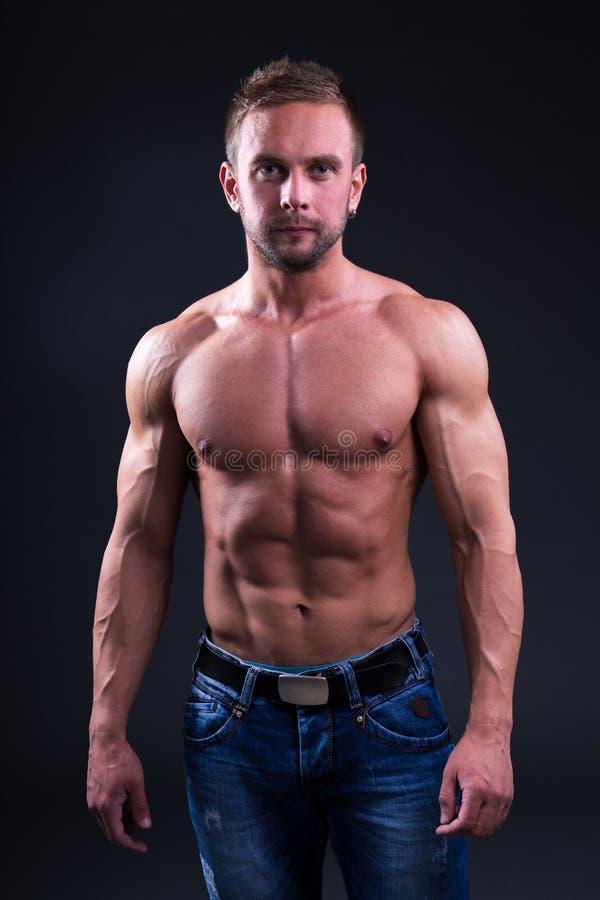 站立在黑暗的背景的年轻肌肉人画象  免版税库存照片