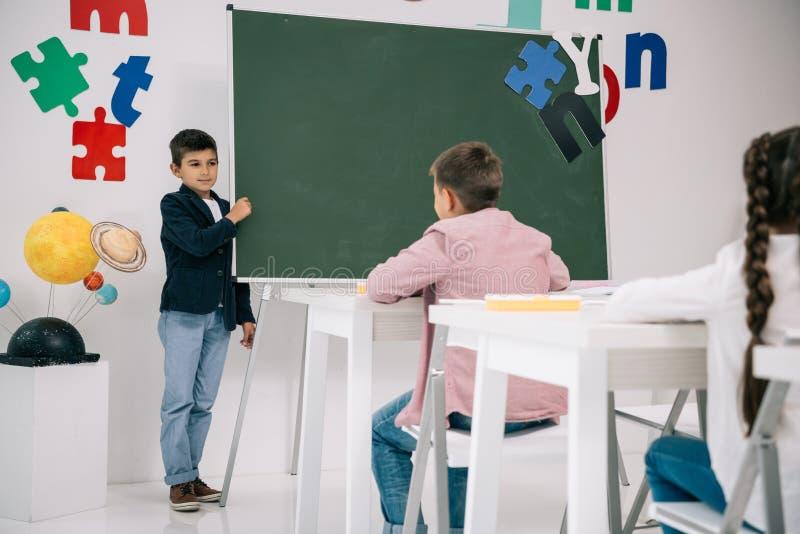 站立在黑板和看同学坐的男小学生 库存图片