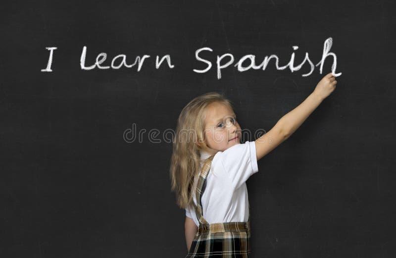 站立在黑板的甜小辈女小学生愉快的文字我学会西班牙语 库存图片
