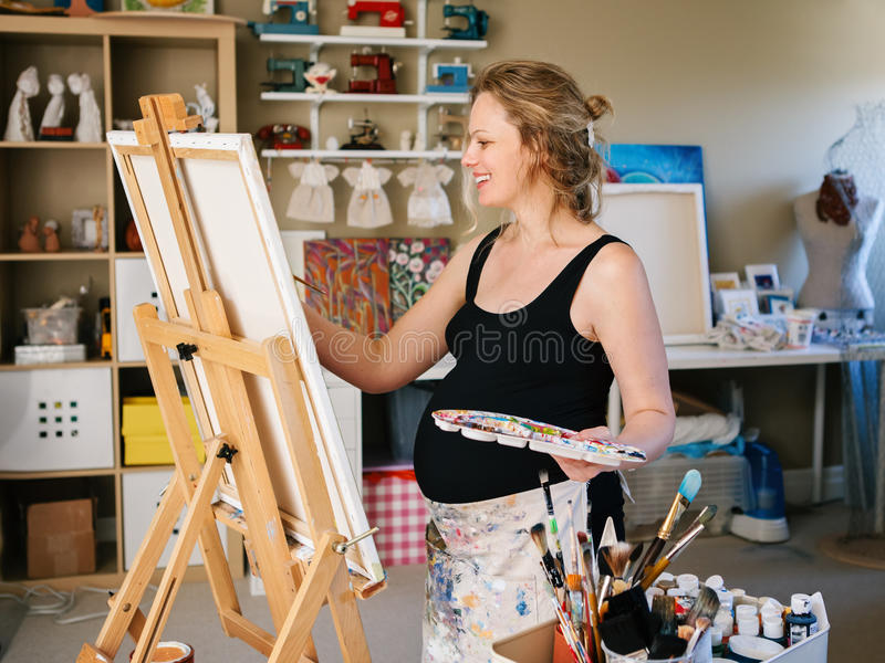 站立在画架的微笑的白色白种人年轻孕妇图画绘画画象在家庭演播室 库存照片