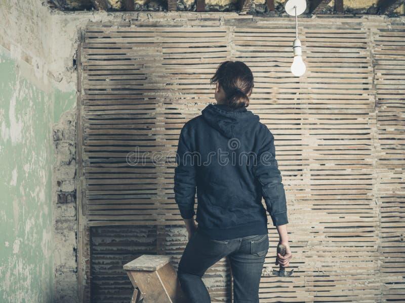 站立在活梯的妇女在篱笆条和涂抹墙壁旁边 免版税库存图片