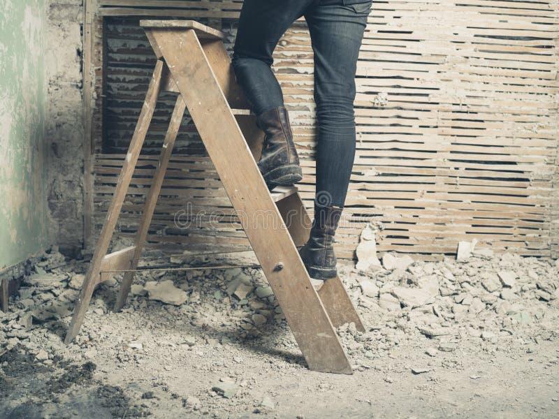站立在活梯的妇女在篱笆条和涂抹墙壁旁边 库存照片