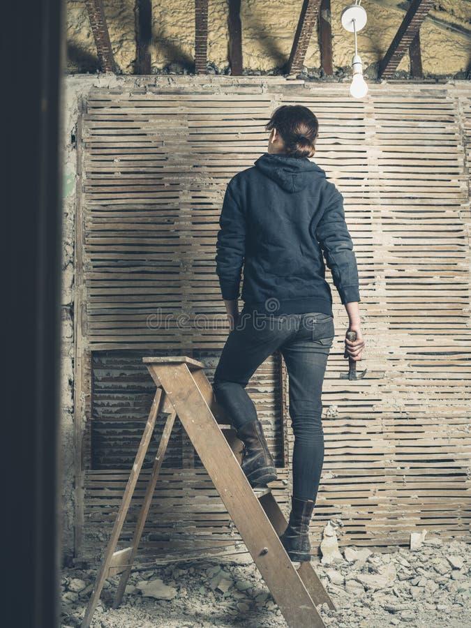 站立在活梯的妇女在篱笆条和涂抹墙壁旁边 免版税库存照片