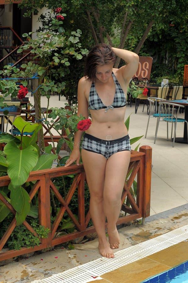 站立在水池边缘的少妇 免版税库存图片
