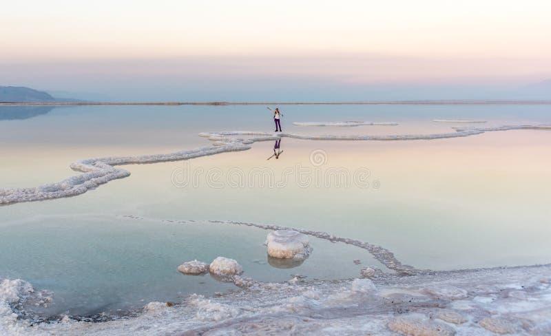站立在死海的妇女在日落 免版税库存图片
