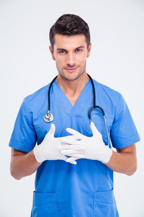 站立在医疗手套的微笑的男性医生 免版税库存图片