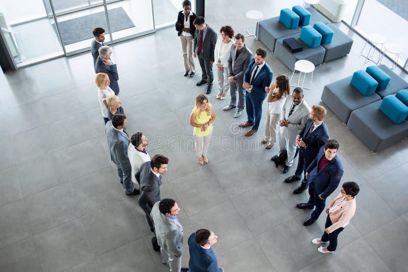 站立在他的伙伴前面的微笑的领导鼓掌 免版税图库摄影